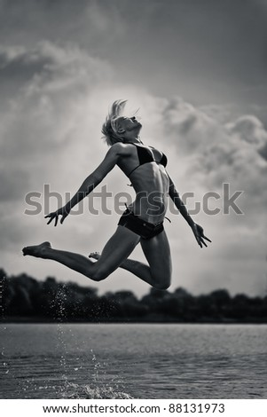 young woman jumping out of water.black and white - stock photo