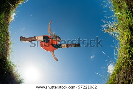 young woman jumping over a creek; shot from below