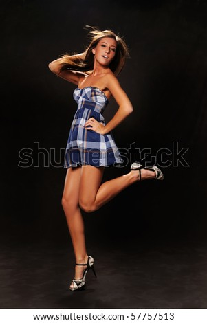 Young woman jumping over a dark background