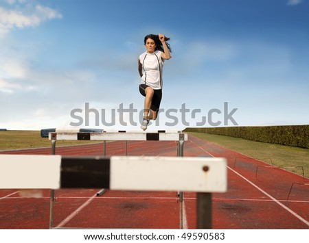 Young woman jumping over an obstacle on a running track - stock photo