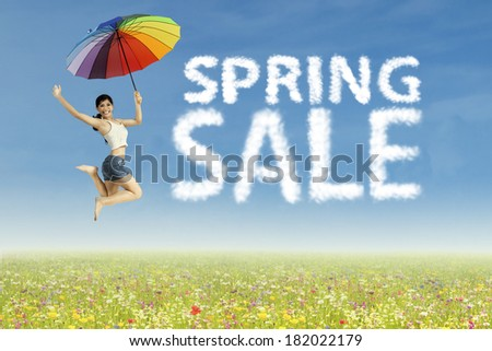Young woman jumping with clouds shaped of spring sale - stock photo