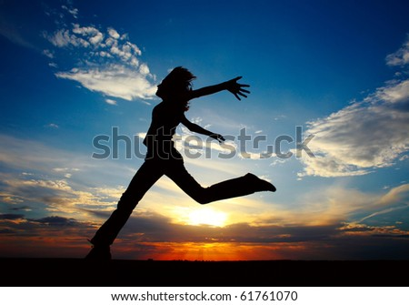 Young woman jumping with raised hands - stock photo