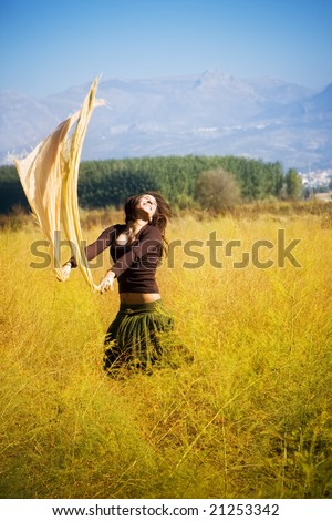 Young woman jumping with scarf in a field. - stock photo