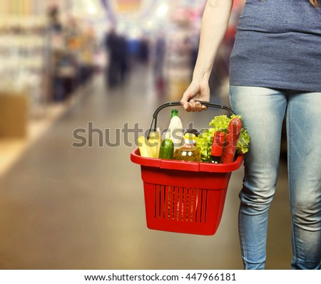 Young woman keeps shopping basket with food and drinks in the store - stock photo