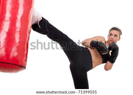 young woman kick a punching bag- isolated on white - stock photo