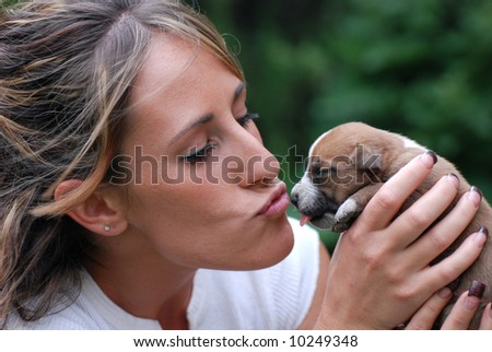 Young Woman kissing a puppy - stock photo