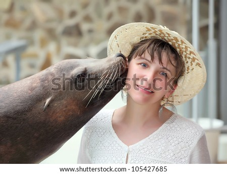 Young woman kissing a seal at the zoo.