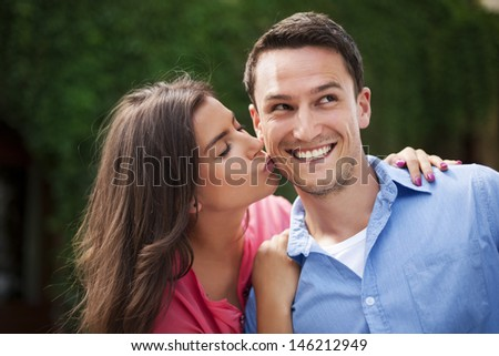Young woman kissing her boyfriend on the cheek - stock photo