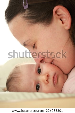 Young woman kissing her lovely baby - stock photo