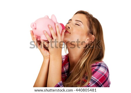 Young woman kissing piggy bank  - stock photo