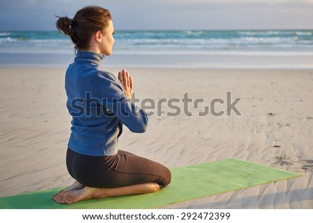 Young woman kneeling on her yoga-mat with her hands together meditating on an early morning beach - stock photo