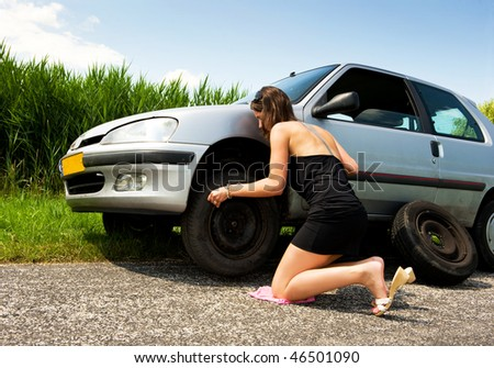 Young woman, kneeling to tighten the bolts on a spare tire - stock photo