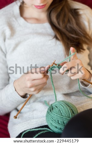 Young woman knitting at home - stock photo