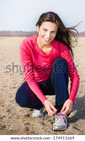 Young woman lacing her running shoes before jogging