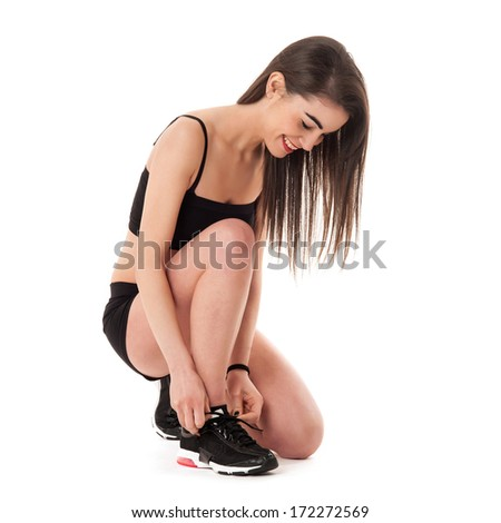 Young woman lacing her shoes isolated against white background.  - stock photo