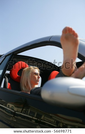 Young woman laid in a car - stock photo
