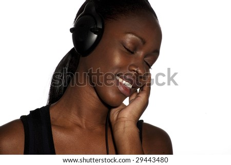 Young woman laughing happily while listening to music - stock photo