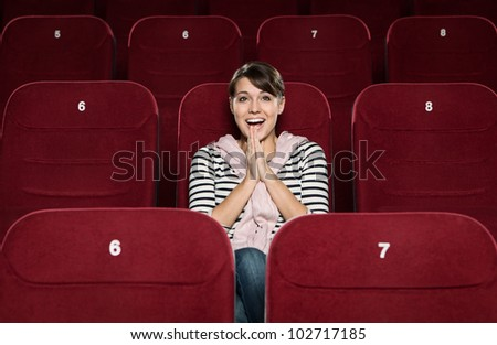 Young woman laughing in the movie theater - stock photo
