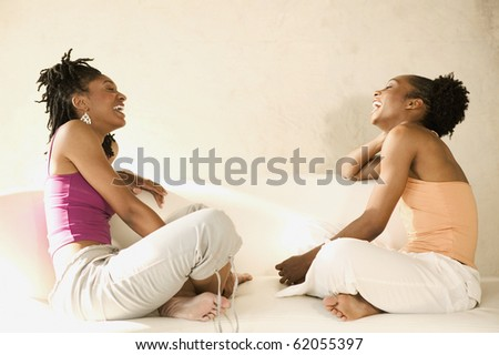 Young woman laughing together - stock photo