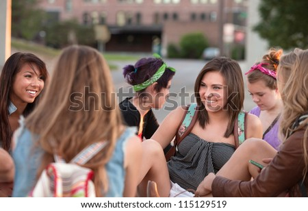 Young woman laughing with her friends sitting outside - stock photo