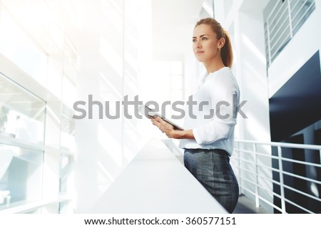 Young woman lawyer dreaming about something while standing with portable touch pad in modern office interior, female skilled managers thinking about new business ideas while work on digital tablet - stock photo