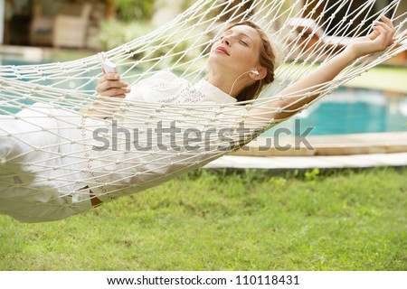 Young woman laying and relaxing on a white hammock in a tropical garden near a swimming pool, listening to music with headphones. - stock photo