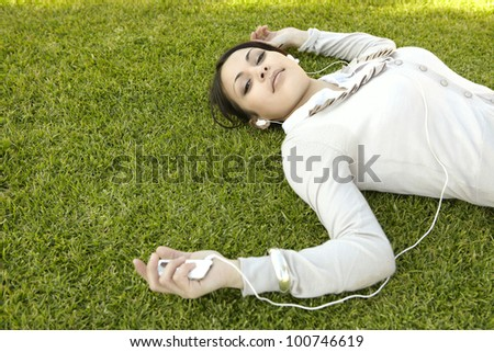 Young woman laying down on green grass, listening to music with headphones, smiling. - stock photo
