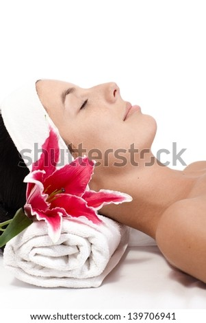 Young woman laying eyes closed, receiving beauty treatment, side view.