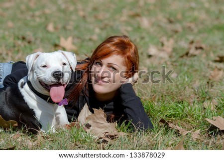 Young woman laying in a park with her amstaff pet dog