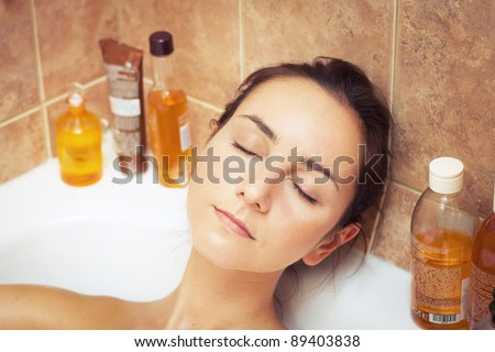 Young woman laying in bathtub full of foam - stock photo