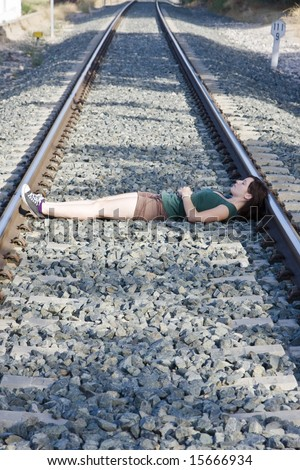 Young woman laying on a railway. - stock photo
