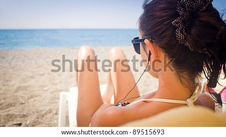 Young woman laying on a sun-bed on the beach - stock photo