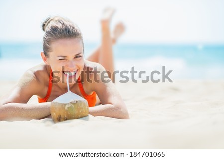 Young woman laying on beach and drinking coconut milk - stock photo