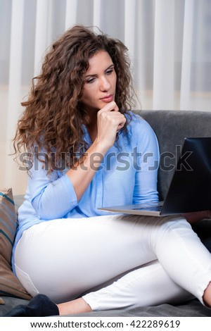 Young woman laying on couch and using laptop, looking at camera.