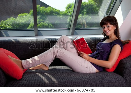 young woman laying on couch reading a book 6780