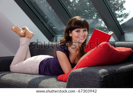 young woman laying on couch reading a book