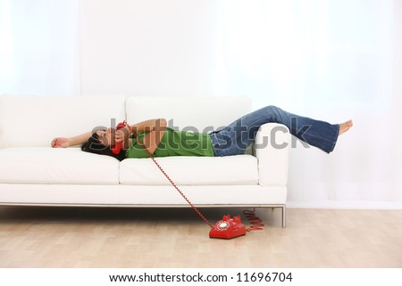 Young woman laying on couch talking on red retro telephone - stock photo