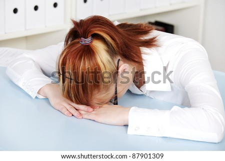Young woman laying on the desk in the office.