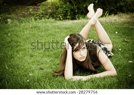 Young woman laying on the grass - stock photo