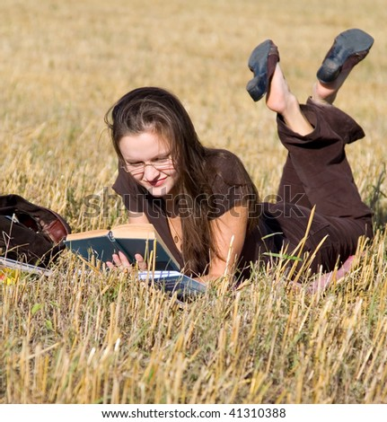 Young woman lays on yellow field and reads book.