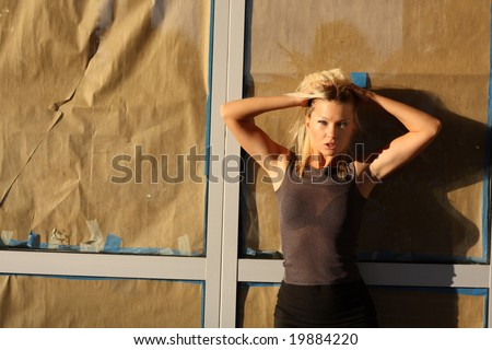 Young woman leaning against a glass window