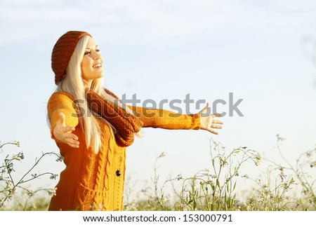 Young woman leaning against a tree - stock photo