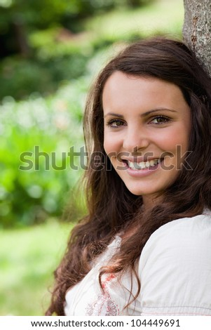 Young woman leaning against a tree in the countryside while showing a great smile - stock photo