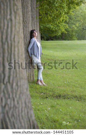 young woman leaning against a tree in the park