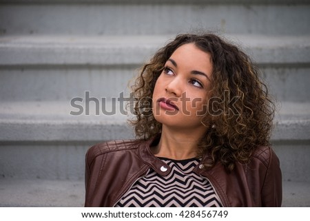 Young woman leaning backwards on steps, looking up in the sky, day dreaming - stock photo