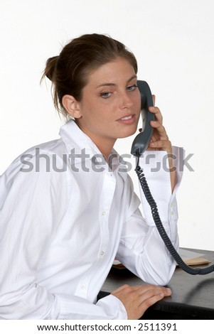 Young Woman Leaning Elbow on Desk Talking on Phone - stock photo