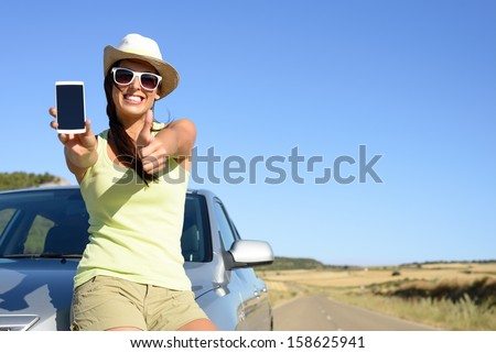 Young woman leaning on car showing cell phone screen and doing thumbs up gesture. Positive woman giving her approval to car insurance service. - stock photo