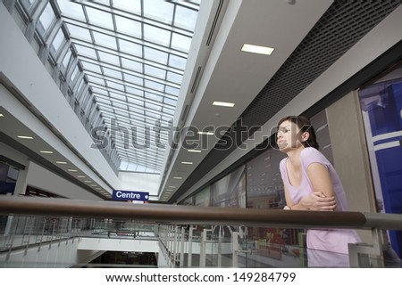 Young woman leaning on railing in shopping centre - stock photo