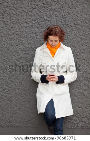 Young woman leaning on wall looking at her cell phone - stock photo