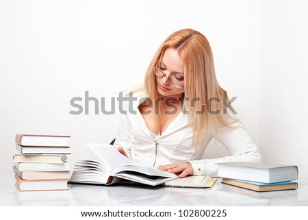 Young woman learning at table with a lot of books - stock photo